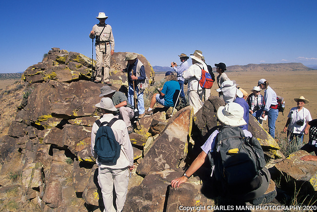 A participants in a field trip sponsored by a local museum examine petroglyphs scattered along a rocky ridge in the Galesteo River Basin near the village of Galesteo, New Mexico