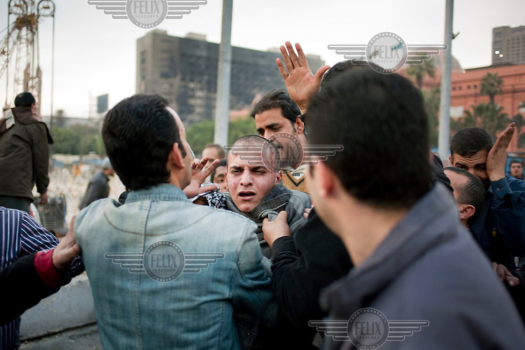 A young Mubarak supporter captured by anti-government protesters is beaten before being taken away outisde the Egyptian Museum in Tahrir Square. Continued anti-government protests take place in Cairo calling for President Mubarak to stand down. After dissolving the government, Mubarak still refuses to step down from power.