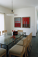 Elegant dining chairs line a glass-topped table in this contemporary dining room