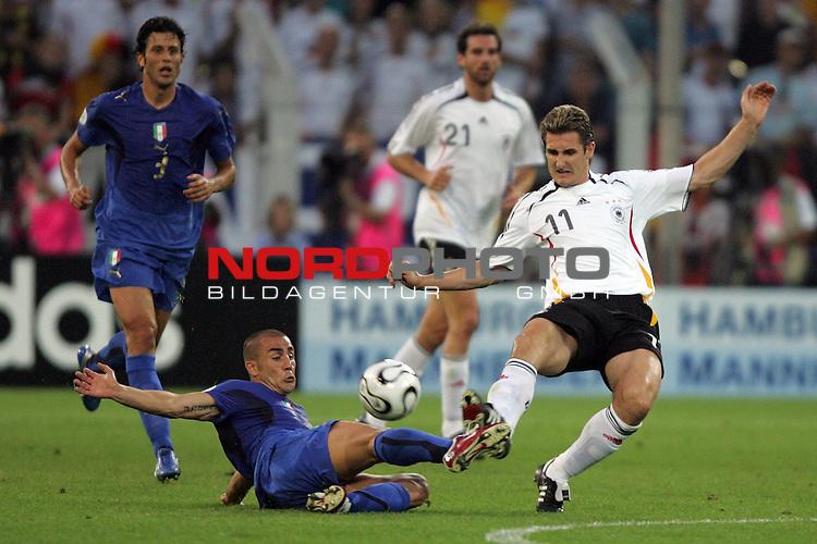 FIFA WM 2006 -  Semi Finals / Halbfinale<br /> Play    #61 (04-Juli) - Deutschland - Italien<br /> <br /> Miroslav Klose (rechts) von Deutschland im Zweikampf mit Fabio Cannavaro (am Boden) von Italien.<br /> <br /> Foto &copy; nordphoto