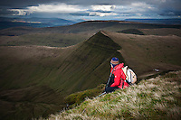 Female hiker enjoys mountain view from summit of Pen Y Fan, Brecon Beacons national park, Wales