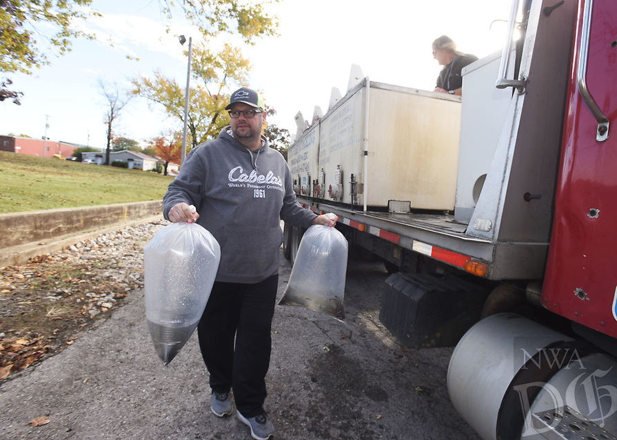 NWA Democrat-Gazette/FLIP PUTTHOFF <br />CARRYIN' AN AQUARIUM<br />J.R. Pitts of Garfield carries fish he bought Wednesday Nov. 7 2018 at Webb's Feed and Seed store in Pea Ridge from Tracy Jackson (right) with the fish company, Arkansas Pond Stockers, Inc. Pitts bought catfish and grass carp to stock in ponds on his property. Arkansas Pond Stockers of northeast Arkansas stops at the feed store in downtown Pea Ridge once a month to sell fish for customers to stock their ponds and lakes. They sell hybrid bluegill, catfish, grass carp, minnows and other species.