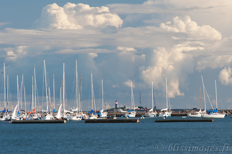 Cumulonimbus clouds dance in ominous patterns over Harmaja lighthouse, as seen from the sailboat docks of Helsinki harbour, Finland.
