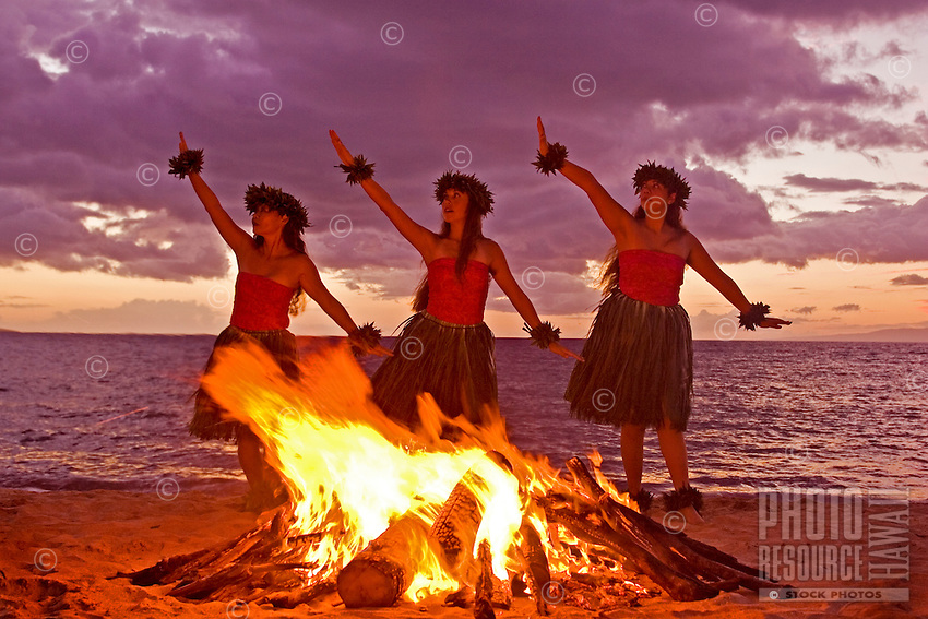 Three hula dancers perform a dance for Pele next to a fire at Makena, Maui.