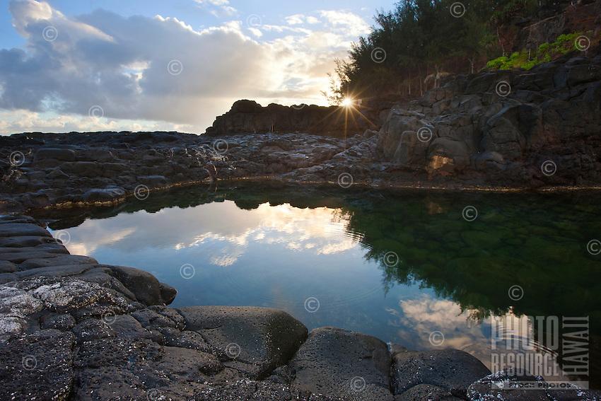 A very still morning renders Queens Bath a mirror as the sun peers through the trees on Kauai.