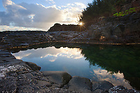 A very still morning renders Queens Bath a mirror as the sun peers through the trees on Kauai.