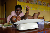 Kroo Bay, Freetown, Sierra Leone...Story on child and maternal health in the Kroo Bay slum community in Freetown, Sierra Leone, which has the World's worst infant and maternal mortalitly rates. One in 4 children die before they reach the age of 5 and one in 6 mothers dies during child birth (in the UK, the rate is one in 3,800)...The Kroo Bay Community Health Centre has a catchment area of over 8,000 people but lacks adequate facilites to provide even basic care. The clinic lacks even the basics, such as bedpans, surgical spirits and cotton wool. It has no electricity and clean drinking water must be fetched from the nearby well everyday...Aminata S Kama weighs Alisan Bangura (15 months) as part of his one month checkup following his vaccinations at the clinic...© 2007 Aubrey Wade. All rights reserved.