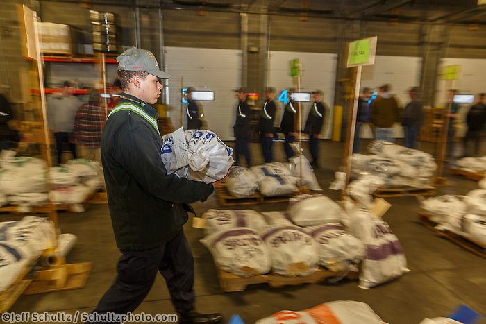 An Iditarod volunteer moves a food drop bag to its proper location as others unload, weigh, organize and stack the mushers food bags destined for the checkpoints on the 2017 Iditarod at the Airland Transport warehouse facilities in Anchorage Alaska.Wednesday February 15, 2017.<br /> <br /> <br /> <br /> Photo by Jeff Schultz/SchultzPhoto.com  (C) 2017  ALL RIGHTS RESVERVED