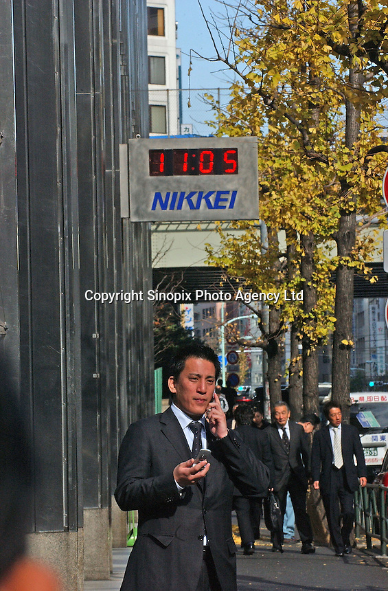 Businessmen under a sign for the tokyo Nikkei, Japan's leading financial newspaper, in Japan's main business and financial district known as Otemachi, Tokyo, Japan..01. Jan 2005