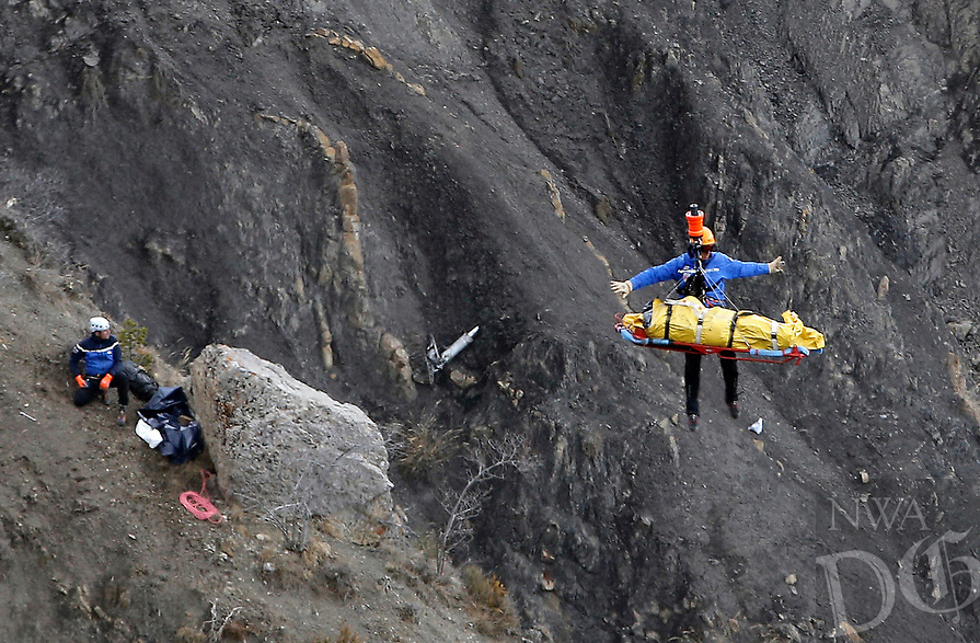 A rescue worker is lifted into an helicopter at the crash site near Seyne-les-Alpes, France, Thursday, March 26, 2015. The co-pilot of the Germanwings jet barricaded himself in the cockpit and ÏintentionallyÓ rammed the plane full speed into the French Alps, ignoring the captainÌs frantic pounding on the cockpit door and the screams of terror from passengers, a prosecutor said Thursday. In a split second, he killed all 150 people aboard the plane. (AP Photo/Laurent Cipriani)