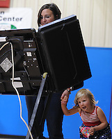 NWA Democrat-Gazette/ANDY SHUPE<br /> Evie Mihalevich, 3, looks beneath the voting machine Tuesday, Sept. 15, 2015, as her mother, Katie Mihalevich, votes in the school board election at the Yvonne Richardson Community Center in Fayetteville. Katie Mihalevich said that she told Evie that the were going voting, but she misunderstood and thought they were going to go boating.