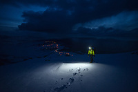 Female hiker hiking by headlamp to basecamp in winter near Matmora, Delp, Austvågøy, Lofoten Islands, Norway