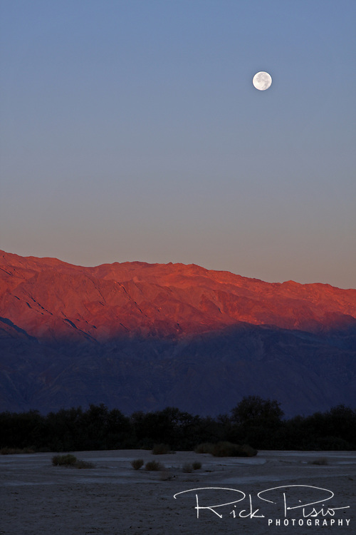 A full moon descends towards the Panamint Range at sunrise in Death Valley National Park.