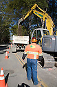 A worker watches an excavator dump dirt into a truck. The cities of Palo Alto and Mountain View are jointly constructing a reclaimed water pipeline to carry recycled water from the Palo Alto Regional Water Quality Control Plant to customers along East Bayshore Parkway and Mountain View's North Bayshore area.
