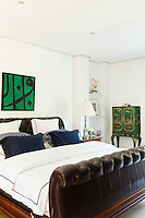 The white bedroom has a upholstered leather sleigh bed with blue and white bed linen. A lamp stands on a bedside table. A green Japanese style cabinet stands against one wall.