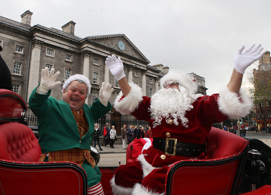 ****NO FEE PIC ******.19/11/2011.Santa Claus & Bubbles the Elf pass Trinity College during a Christmas Parade.at the opening of Santa's Playland in The Ambassador Theatre,Dublin.One of this Christmas' biggest events is coming!  Santa's Playland takes up residence at The Ambassador Theatre in preparation for this year's festive season.  The spectacular event opens on Saturday 19 November and runs until Friday 23 December. Santa's Playland will see children transported to a magical Christmas paradise.On entering Santa's Playland children will be treated to a special Christmas play time.  The Play Area is full of Christmas treats with bouncy castles, slides and Christmas displays..Photo: Gareth Chaney Collins