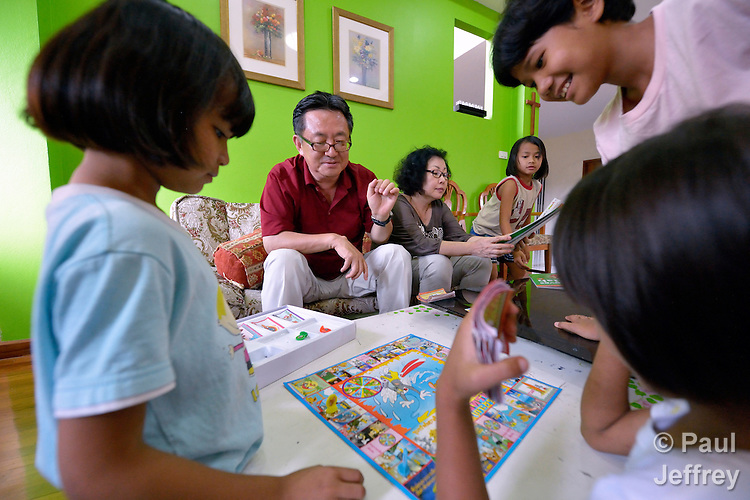 Gary Moon, a United Methodist missionary in Thailand, plays the Thai version of Monopoly with girls in an orphanage he founded with his wife Cindy (in the background) in Chiang Mai. The girls are orphans, and are all HIV positive.