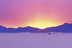 Sun setting behind Victoria Peak with the sand dunes, White Sands National Monument, Alamorgodo, New Mexico, USA .  John offers private photo tours in Arizona and and Colorado. Year-round.