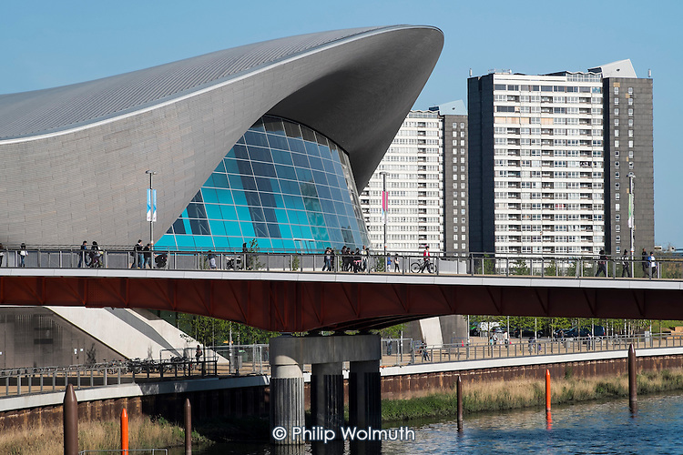 The Aquatic Centre designed by Zaha Hadid at the Queen Elizabeth Olympic Park, Stratford, and Carpenters Road Estate tower blocks.