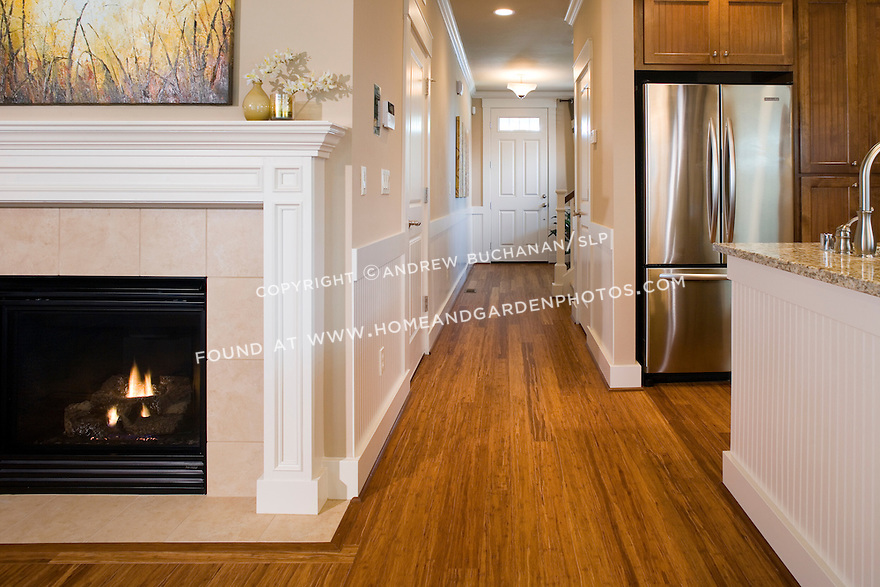 A glowing fire in the fireplace and gleaming hardwood floors highlight this family room space immediately off the kitchen as we look down the long entrance hallway toward the front door in a builder spec home and prove that small, townhouse-style houses don't have to be short on features.