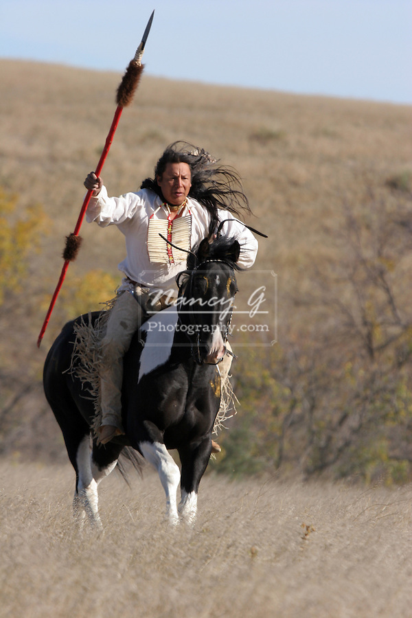 A Native American Sioux Indian on Horseback running with a spear in attack mode