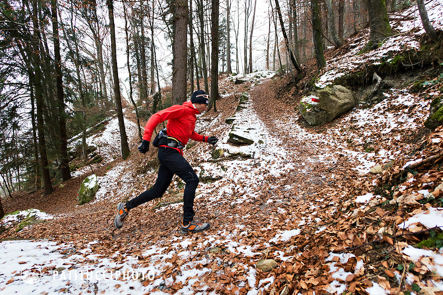 Ueli Steck trail running on a cold winter day in a forest with snow lined trails