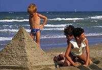 Giochi sulla spiaggia, bambini costruiscono una piramide con la sabbia.Children on the beach, building a sand pyramid