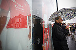 A man sheltering from the rain under an umbrella outside the club shop near the City Ground, Nottingham before Nottingham Forest take on visitors Ipswich Town in an Npower Championship match. Forest won the match by two goals to nil in front of 22,935 spectators.