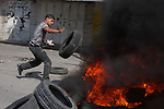Palestinian youths burn wheels during clashes at the Kalandia checkpoint near the West Bank city of Ramallah October 9, 2009. Palestinian leaders on Thursday called for a one-day general strike and warned of more street protests over Jerusalem, where clashes at the flashpoint al-Aqsa mosque two weeks ago cranked up tensions in the disputed city. Israel is playing down Palestinian warnings that its security tactics risk a new Palestinian uprising. Photo by Issam Rimawi