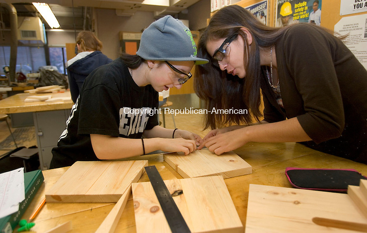 TORRINGTON, CT. 07 December 2012-120712SV04-From left, Victoria Kerr, 17 and Gloria Portillo, 15, both of Torrington measure parts for a step stool during a wood class at the high school in Torrington Friday. Torrington High School technology arts teacher Scott Samsel started a wood shop class for girls only this year. Wood shop is an elective in high school and designed to help girls become interested in a field dominated by men. .Steven Valenti Republican-American