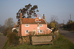 Pretty pink washed rural cottage and village sign, Marlesford, Suffolk, England