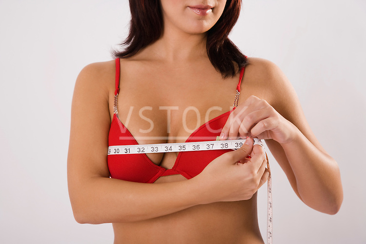Young woman in underwear measuring chest with tape measure, mid section