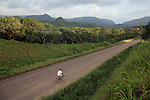 BELIZE - SEPTEMBER 10, 2007:  A man rides his bike down the Hummingbird Highway trough a citrus grove south of Caves Branch on September 10, 2007 in Belize.  (PHOTOGRAPH BY MICHAEL NAGLE)