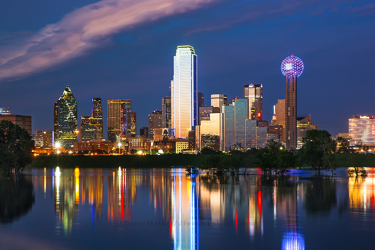 Illuminated by a blend of ambient and artificial light, sunset shimmers off the Dallas skyline as the city is reflected back in the flooded Trinity River. As the sun dips below the horizon, Bank of America Plaza (centered) glows neon blue and yellow, while lights on the iconic Reunion Tower (far right) flash and sparkle, bringing the city to life as the night quickly approaches.