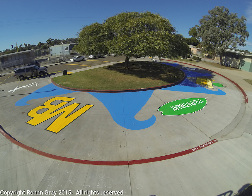Mission Bay High School, San Diego CA, USA.  Saturday, October 10th 2015:  Mission Bay High School students and community members paint a street mural in front of the High School Gym.  The mural installation was funded by the non-profit organization Beautiful PB throgh a grant from SANDAG.