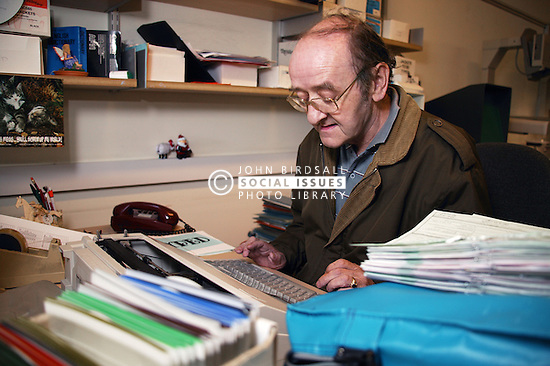 Man with disability working as microfilm technician; sitting at desk in visual communications office using electronic typewriter,