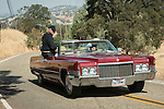 Gail Fairbrother and Bill Lavalle in a red Cadillac convertible lead the Days of '49 wagon train as they travel the back roads of Amador County, Calif., between Amador City and Sutter Creek, Calif.<br /> <br /> Diamond Jubilee commemoration of the founding of Amador County in 1854