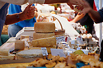 An artisnal cheese stand at the Saturday Portland Farmers' Market on the campus of Portland State University offers samples of it's cheese to customers.