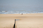 People walking on wide empty sandy beach at Frinton on Sea, Essex, England