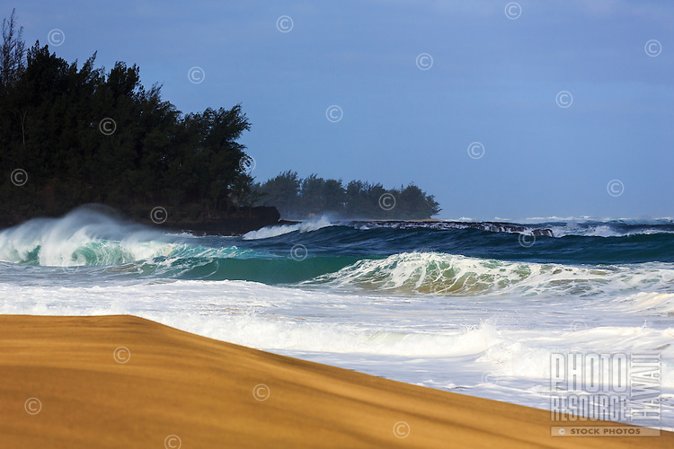 A wave breaks in a perfect circle along the golden sand shoreline of Lumaha'i Beach, Kaua'i.