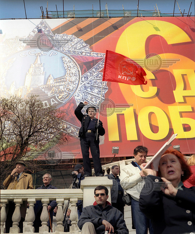 A veteran sailor waves the flag of the Communist party (KPRF) at a May Day rally.