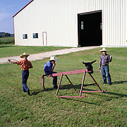 Cowboy Church. Texas, USA. 2007. Children practicing their roping skills on a metal bull outside the barn.