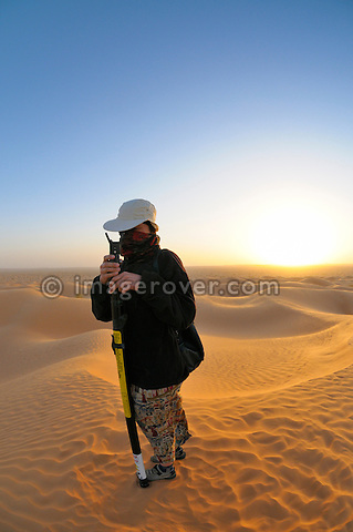 Africa, Tunisia, nr. Ksar Rhilane. Sunrise over Ksar Ghilane in the sand dunes on the eastern edge of the Grand Erg Oriental. Doris preparing a telescopic mast for a photo shooting.  --- No releases available, but releases may not be needed for certain uses. --- Info: Image belongs to a series of photographs taken on a journey to southern Tunisia in North Africa in October 2010. The trip was undertaken by 10 people driving 5 historic Series Land Rover vehicles from the 1960's and 1970's. Most of the journey's time was spent in the Sahara desert, especially in the area around Douz, Tembaine, Ksar Ghilane on the eastern edge of the Grand Erg Oriental.