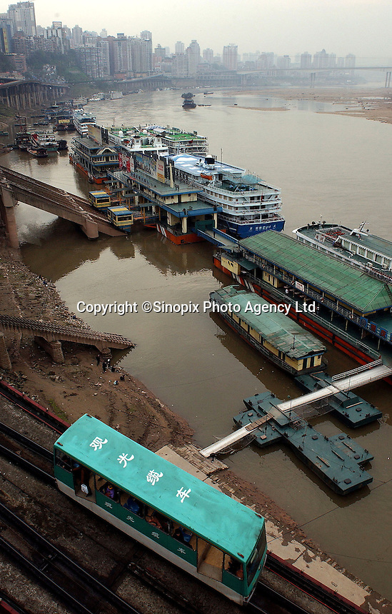 "A tram makes it's way down the steep river bank to the Chaotianmen Port area, ferry terminals and wharf. Chongqing is China's largest city and is often termed a ""super-city"". It is at the far shore of the 600 km long Three Gorges Dam and is the ""gateway to western China"". Large sums of money are being pumped into the area and infrastructural projects and building development is ongoing..16-NOV-04"