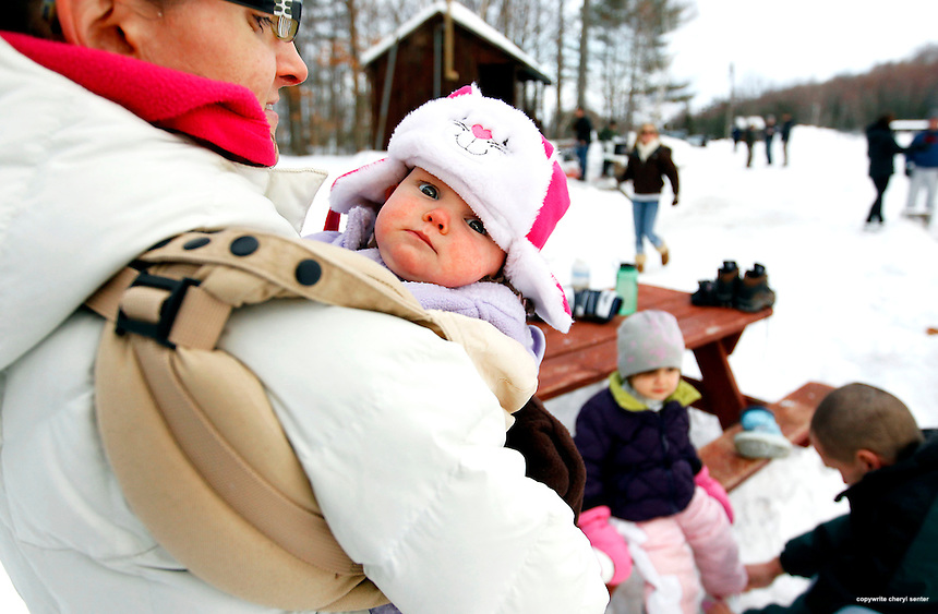 Meaghan Roache holds her nine-month-old daughter Maeve snug in her arms while her husband Tim, bottom right, puts skates on daughter Delaney, 3, at the Winter Whiteout Festival at Stratham Hill Park in Stratham, N.H., N.H. Sunday, Jan. 30,  2011. This was Delaney's first time skating. (Portsmouth Herald Photo Cheryl Senter)