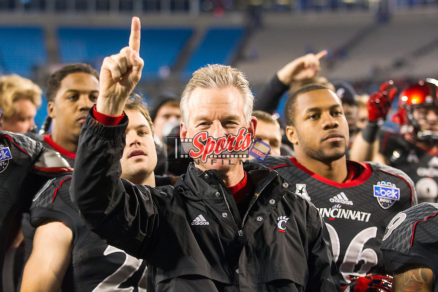 Cincinnati Bearcats head coach Tommy Tuberville salutes the crowd as the band plays the alma mater following the Belk Bowl against the North Carolina Tar Heels at Bank of America Stadium on December 28, 2013 in Charlotte, North Carolina.  The Tar Heels defeated the Bearcats 39-17.   (Brian Westerholt/Sports On Film)