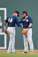 Shortstop Edgardo Fermin (10), left, and second baseman Blake Tiberi (3) of the Columbia Fireflies slap hands before an inning of a game against the Greenville Drive on Tuesday, April 17, 2018, at Fluor Field at the West End in Greenville, South Carolina. Columbia won, 7-5. (Tom Priddy/Four Seam Images)