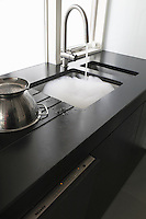 A single-bowl and a half-bowl sink fitted into the Black Zimbabwe granite work top occupy a corner of the kitchen