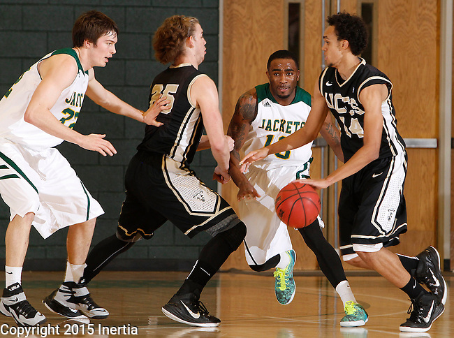 JANUARY 23, 2015 -- Derrick White #14 of UC-Colorado Springs drives past defender Myles Henry of Black Hills State during their Rocky Mountain Athletic Conference men's basketball game Friday at the Donald E. Young Center in Spearfish, S.D.  Also pictured are Riley Ryan #32 of Black Hills State and Alex Welsh #25 of UCCS. (Photo by Dick Carlson/Inertia)