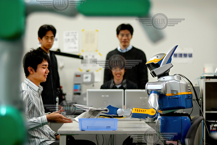 Students work with the HRP2 Robot in Naist, Nara City. An engineer has asked the robot to hand him the newspaper. After a few seconds 'thinking', the robot responds...